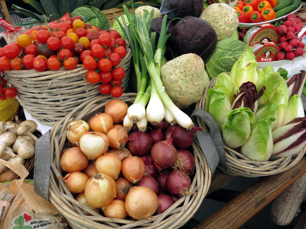 Basket full of vegetables - onions, tomatoes, lettuce, peperes. mushrooms, berries