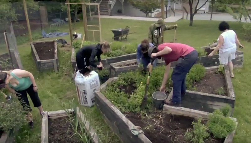 Photo - Students and community members working in garden.
